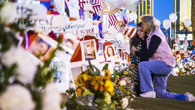 Skylar Carson, 23, left, gets a hug from Midge Elkins as they visit the memorial of 58 crosses at 6 a.m. Oct. 7, 2017, on  Las Vegas Boulevard in Las Vegas after the mass murder a week ago left 58 victims dead and almost 500 wounded.