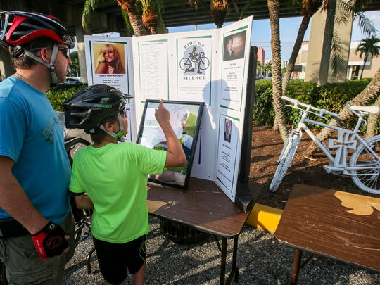 Danny Brown of Cape Coral, and his son, Aidan Brown, 10, look at the memorial that was at the event. The Fort Myers Ride of Silence, sponsored by the Caloosa Riders Bicycle Club took to the streets Wednesday night. Cyclists rode in a silent, funeral-style procession at 10-12 mph for 8 miles to honor those who have been killed or injured while cycling on public roadways. Riders wore black arm bands, or red if they have personally been injured in a cycling vs. motor vehicle accident. May 20, 2015.