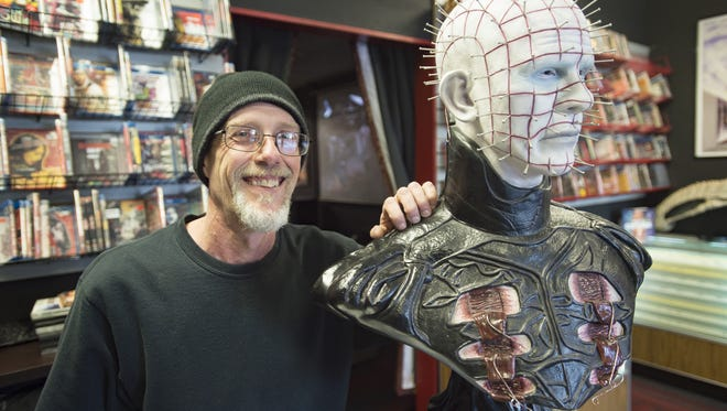 """Jeff Abbott poses for a photo with his prized bust of horror character """"Pinhead"""" at his shop, The Gorehound's Playground on Wednesday, November 8, 2017. Abbott, a collector of horror films and memorabilia, has opened a new retail store with video rental and a theater on W. Drake Road."""
