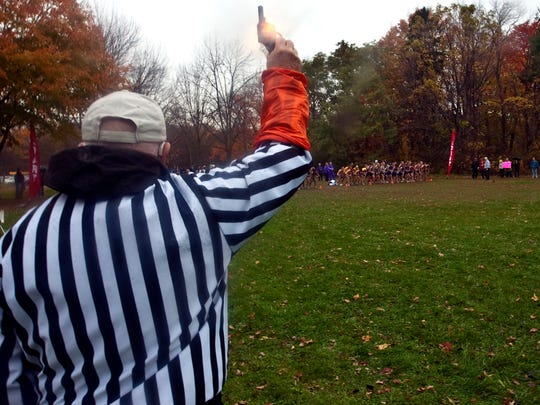 Referee Mel Heimark fires his gun to start the South Milwaukee cross country sectional in 2010.