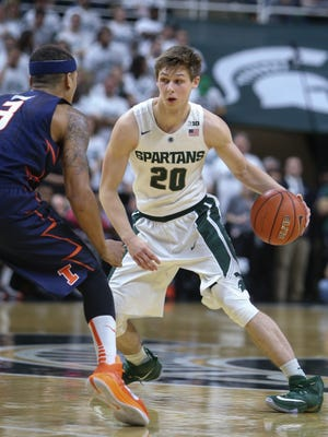 Michigan State Spartans Matt McQuaid drives against the University of Illinois Jaylon Tate during second half action on Thursday, January 7,2015 at the Breslin Center in East Lansing Michigan.