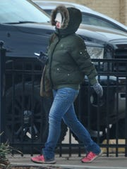 A bundled pedestrian walks near downtown Thursday morning as the low expected temperatures are to dip into 20's.