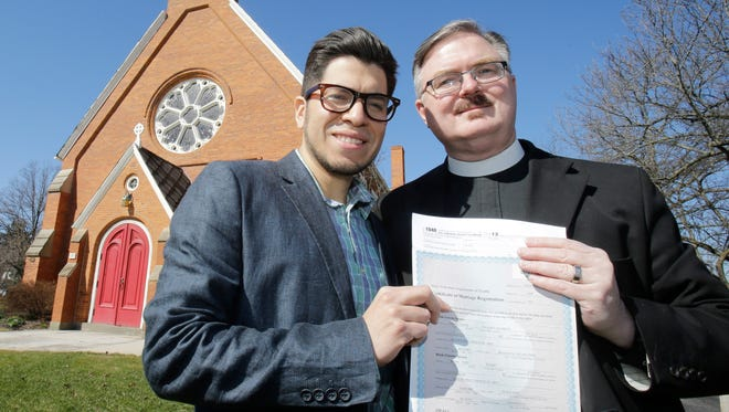 In this photo taken April 4, 2015, Rev. Brian K. Wilbert, right, and Yorki Encalada, hold their marriage certificate and tax forms at the Christ Episcopal Church in Oberlin, Ohio. A necessary burden for most Americans, Tax Day is an accounting nightmare for thousands of gay and lesbian couples as they wrestle with the uneven legal status of same-sex marriage in the United States.  (AP Photo/Tony Dejak)