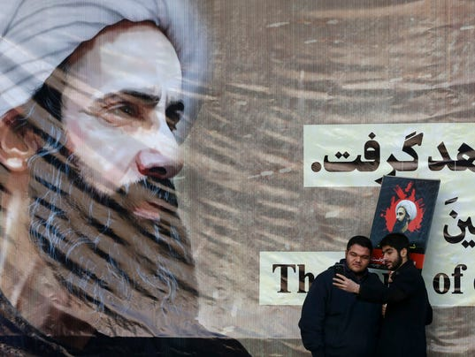 Iranian men take a selfie with a poster of Sheikh Nimr
