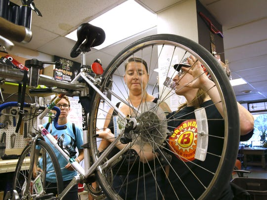 Katie Jesse of Milwaukee (center) and Stacy LaPoint of Shorewood (left) watch as bike mechanic Heather Sewrey explains a how to fix a shifting problem on Jesse's bike.