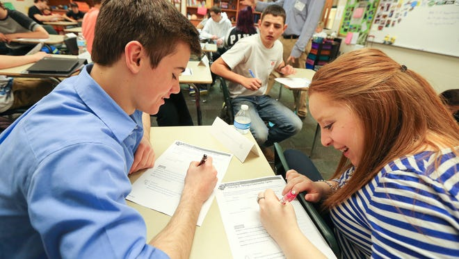 John McCaffrey, left, Jarrett Batliner, center, and Reagan Caufield, right, work together on a project discussing feelings of safety as part of a group exercise at Floyd Central High School.March 18, 2016