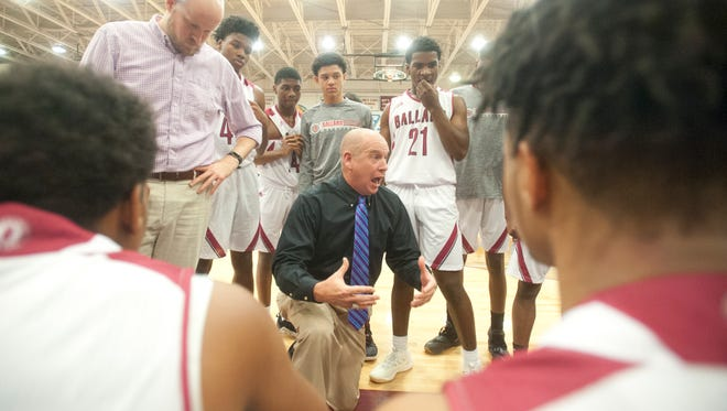 Ballard head basketball coach Chris C. Renner talks to his players during a time-out.