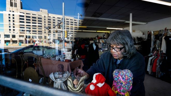 Cleveland Street Flea Market booth owner Jessie M. Payne places some of her knick knacks for sale closer to the window, where the new Crosstown Concourse building is reflected. Payne, who had as many as 14 booths in the flea market is preparing for the final weekend of the market, which will officially close on Sunday.