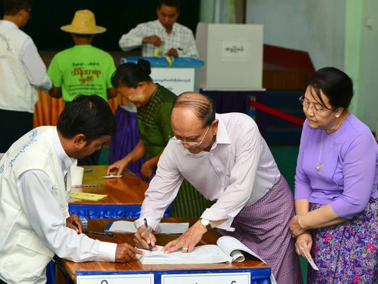 Myanmar's President Thein Sein, second right, signs