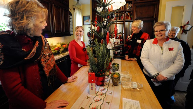 In this file photo, homeowner Tina Schram, second from left, laughs with sister Heidi LaCosse, left, as they talk with visitors in the 26th annual Manitowoc Symphony Orchestra Holiday Tour of Homes in 2014.