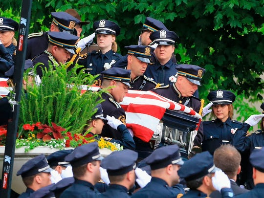 Police officers carry the casket of Omaha Police Officer Kerrie Orozco out of St. John's Catholic Church in Omaha on Tuesday. Police killed on the job nearly doubled between 2013 and 2014, according to a report.