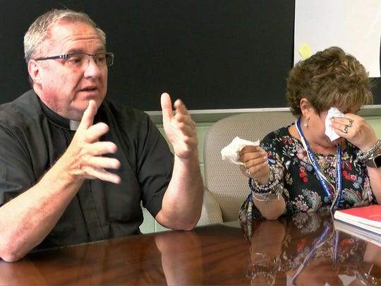 """""""We're an Easter people, but every classroom has a cross. And that's part of our life, too,"""" says the Rev. G. Scott Shaffer, the pastor of St. Joseph's Parish, discussing the recent death of drama director Karin Krenek with JoAnn D'Anton, the school's marketing director."""