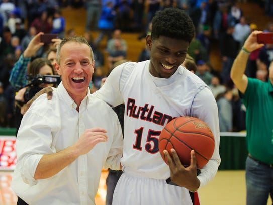 Rutland coach Mike Wood gives the game ball to Rutland's Noah Tyson (15) during the Division I boys basketball championship game between the Mount Mansfield Cougars and the Rutland Raiders at Patrick Gym on March 17.