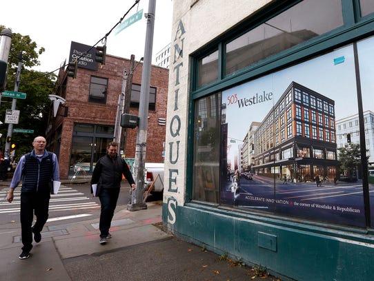 Pedestrians walk past a former antique shop, now a