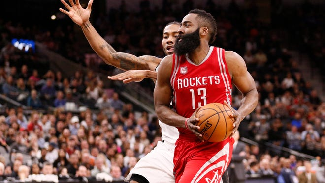 Houston Rockets shooting guard James Harden (13) drives to the basket while guarded by San Antonio Spurs small forward Kawhi Leonard (behind) during the second half at AT&T Center.
