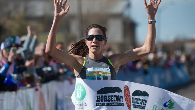 Annmarie Kirkpatrick becomes the first female runner to cross the finish line during the Horsetooth Half Marathon on Sunday.