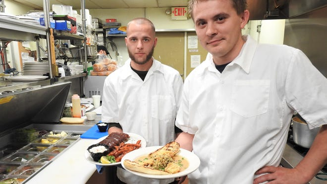 Head Chef Colin Kotab (front) holds the seafood etoufee with rice pilaf and fried oysters and Sous Chef Walter Larimer displays the smoked ribs with sweet potato fries and coleslaw. Those dishes highlight an array of options on the menu at Muddy Misers.