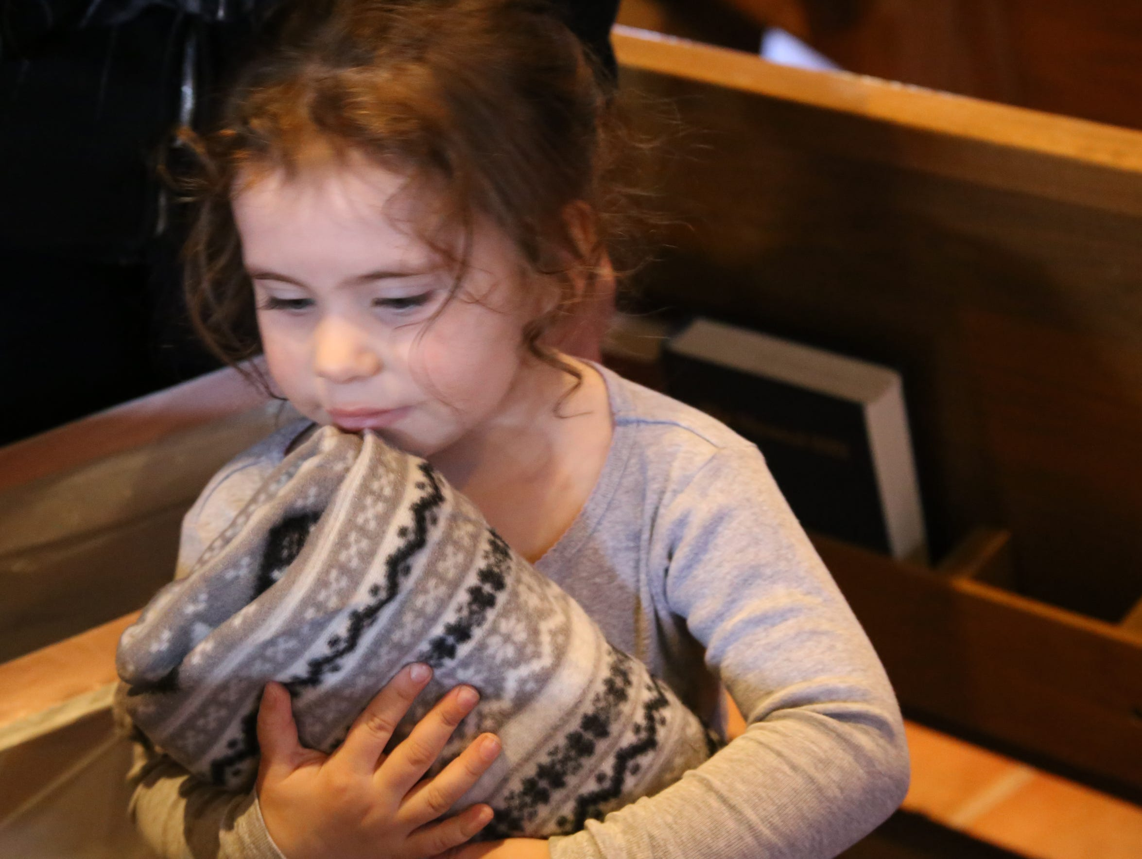 A child holds a blanket she received at a Christmas
