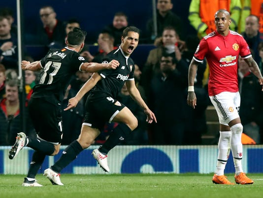 Sevilla's Wissam Ben Yedder, center, celebrates scoring his side's first goal of the game during the Champions League round of 16 second leg soccer match between Manchester United and Sevilla, at Old Trafford in Manchester, England, Tuesday, March 13, 2018. Sevilla won the game 2-1 and go through to the quarterfinals. (Martin Rickett/PA via AP)