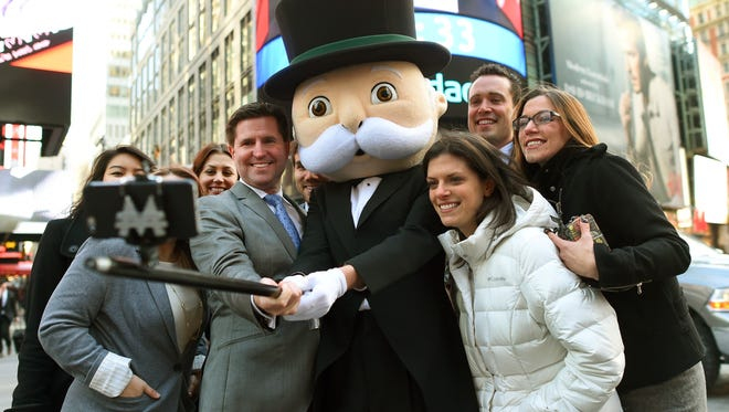Mr. Monopoly uses a selfie stick to take a photo in Times Square with Hasbro staff and senior vice president of global brand strategy and marketing Eric Nyman on Thursday.