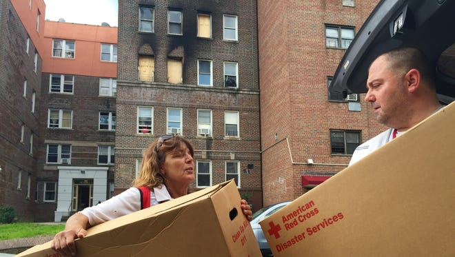 Carolyn Sherwin and Louis Lambros of the American Red Cross help deliver cleaning supplies to the residents of 28 Carlyn Ave. in Yonkers after Monday's fire.