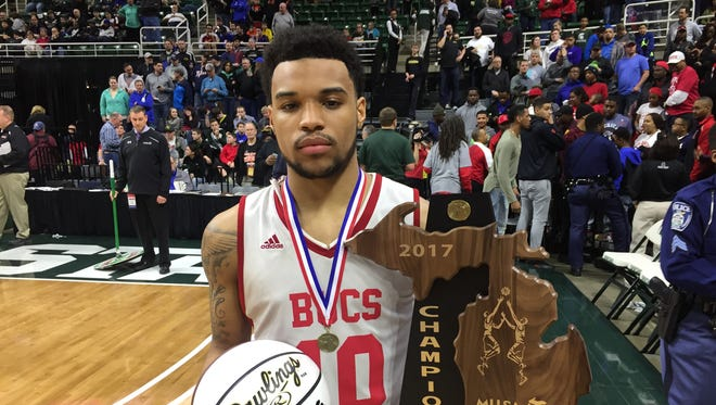 Flint Beecher senior and Eastern Michigan commit Malik Ellison holds the Class C state trophy after his team's 73-58 win over Grand Rapids Covenant Christian at the Breslin Center on Saturday, March 25. Ellison had 32 points.