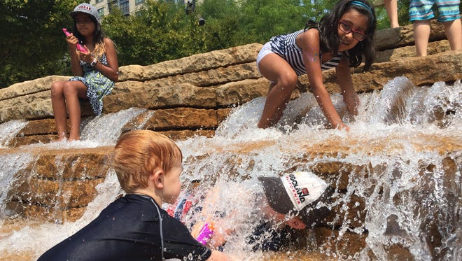 Kids keep cool in a downtown Portland, Oregon, fountain on Aug. 3, 2017, a day that reached 105 degrees.