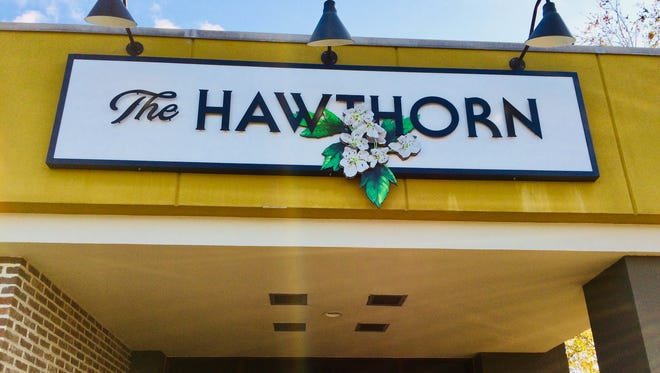 A sign outside The Hawthorn featuring its namesake flower.