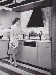 A woman demonstrates the LazyMan rotisserie in this vintage advertisement.