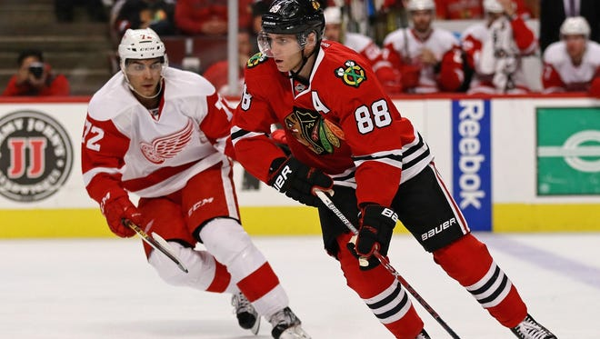Patrick Kane of the Chicago Blackhawks moves past Andreas Athanasiou, left, of the Detroit Red Wings on Oct. 4, 2016, in Chicago.