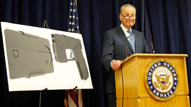 U.S. Sen Charles Schumer, (D-New York), stands beside two photographs of what appears to be a cell phone, but is actually a handgun, during a press conference in his office, Monday, April 4, 2016, in New York.