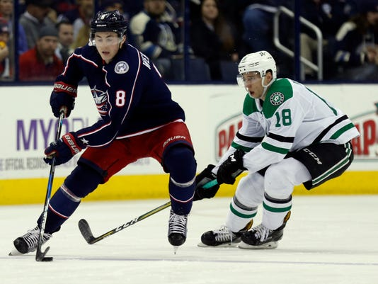 Columbus Blue Jackets defenseman Zach Werenski , left, controls the puck against Dallas Stars forward Tyler Pitlick during the second period of an NHL hockey game in Columbus, Ohio, Thursday, Jan. 18, 2018. (AP Photo/Paul Vernon)