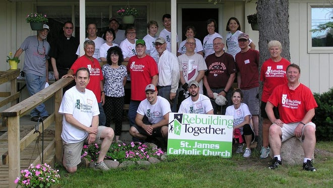 Volunteers from St. James Catholic Church in Novi pose with Wixom homeowner Carol Robinson during Saturday's Rebuilding Together of Oakland County project.