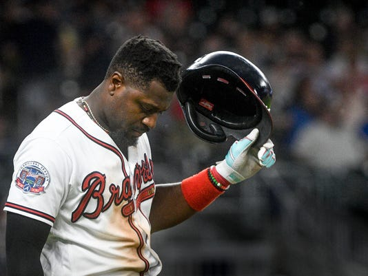 Atlanta Braves' Brandon Phillips takes off his batting helmut and prepares to take the field after getting out with a line fly to center field to end the eighth inning of a baseball game against the Philadelphia Phillies, Tuesday, June 6, 2017, in Atlanta. Philadelphia won 3-1. (AP Photo/John Amis)