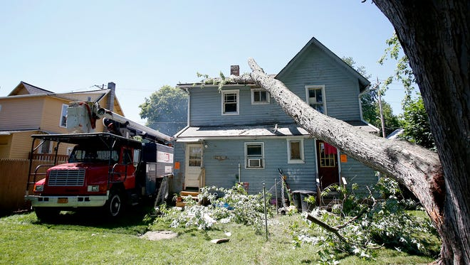 Dave & Sons Tree Service crews work to clear a fallen tree limb that damaged a residence at 240 Home Street in Elmira recently. The structure has been deemed unsafe and unfit to live in.