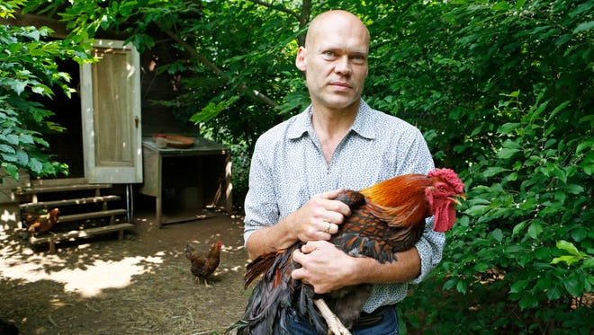 Philippe Gouze holds a rooster in his yard June 24 in New City. Gouze, the general manager of Blue Hill at Stone Barns, raises chickens at his home.