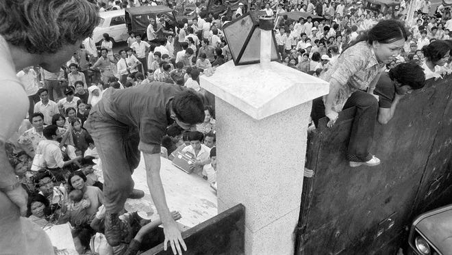 South Vietnamese civilians scale the 14-foot wall of the U.S. embassy in Saigon, trying to reach evacuation helicopters as the last Americans depart from Vietnam, April 29, 1975.