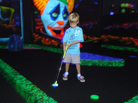 A child tries his hand at Monster Mini Golf.