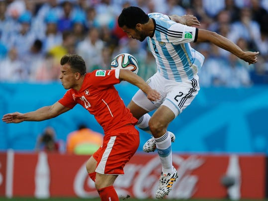 Switzerland's Xherdan Shaqiri, left, and Argentina's Ezequiel Garay go for a header during their World Cup round of 16 soccer match at the Itaquerao Stadium in Sao Paulo, Brazil, Tuesday, July 1, 2014. (AP Photo/Kirsty Wigglesworth)