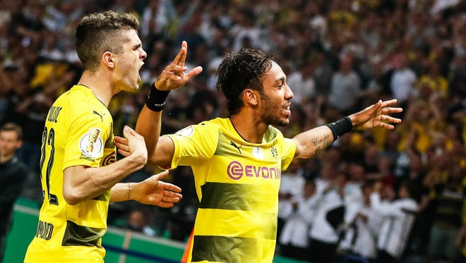 Dortmund's Pierre-Emerick Aubameyang (R) celebrates with his teammate Christian Pulisic (L) after scoring the game-winning goal from the penalty spot during the German Cup final.