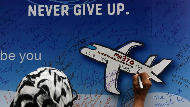 A woman writes messages for the passengers of missing Malaysia Airlines flight MH370 on a banner during a remembrance ceremony to mark the second anniversary of the plane's disappearance, in Kuala Lumpur, Malaysia, March 6, 2016.