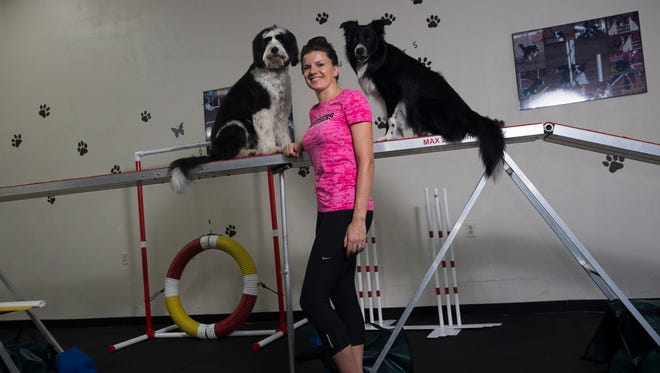 Aschley Kezeske, co-owner of Rufflers Dog University, with her two pups Addison, a Bearded Collie mix, and Skyy, a Border Collier inside of the indoor training facility Kezeske use to train her dogs and those of her clients.