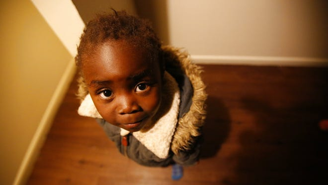 Moza Ausa, a 4-year-old refugee from the war-torn Democratic Republic of Congo, stands in the family's new apartment in Columbus, Ohio, during the early morning hours of Thursday, Feb. 22.. The family, including six children, had just flown to Columbus from Africa. The DRC is not included in the Trump administration's travel ban.
