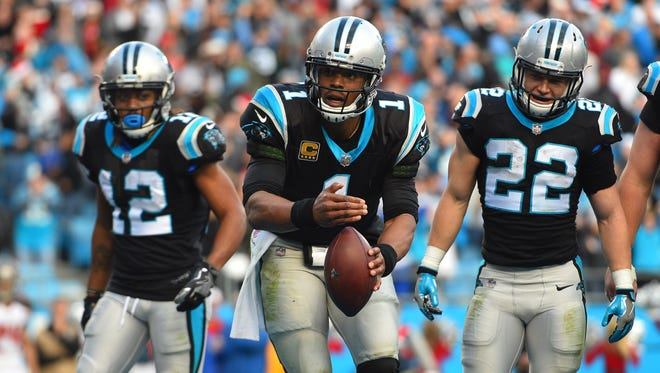 Carolina Panthers quarterback Cam Newton pretends to light a candle on top of the football after scoring a touchdown in the fourth quarter at Bank of America Stadium.
