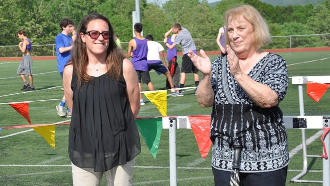 Betsy Evans, right, claps for Sheri Felenstein Dempsey as they are announced as new members of the Rockland Track Hall of Fame during  last week's county track championships.
