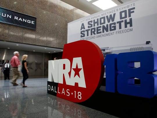 People walk by NRA convention signage in the Kay Bailey