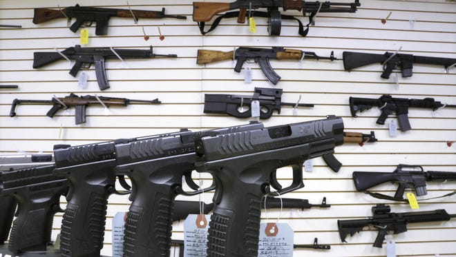 AP file photo of assault weapons and handguns.
