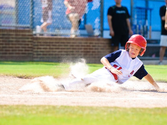 Youth league baseball player sliding home.