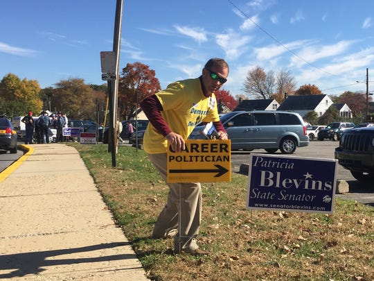 "This man, who declined to give his name, kept putting his ""career politician"" sign next to campaign signs for Patricia Blevins, no matter where her supporters moved the sign, Tuesday morning at Baltz Elementary School in Elsmere."