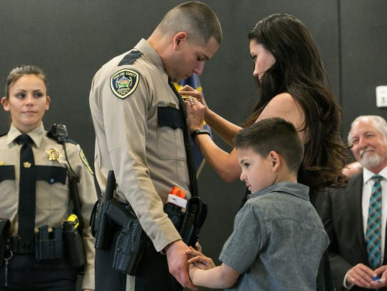 Cadet Jeremy Tellez holds the hand of his  son Braeden,